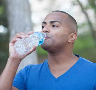 Man outdoors, drinking water from a bottle